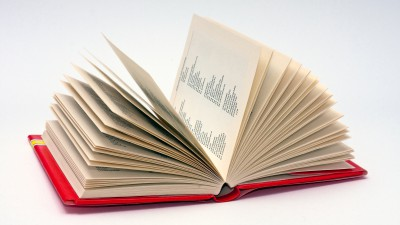 Small format Spanish dictionary, held open on a white background, having it's brownish pages flipped up into the air describing an almost semicircular area. The words and their respective translations are distributed on two columns.